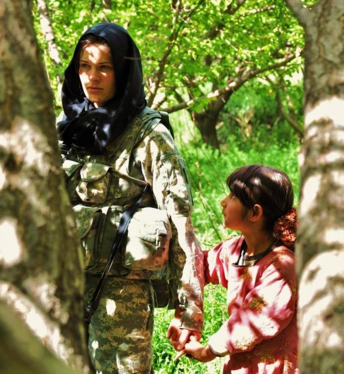 niña tomando la mano de una soldado en medio de un bosque