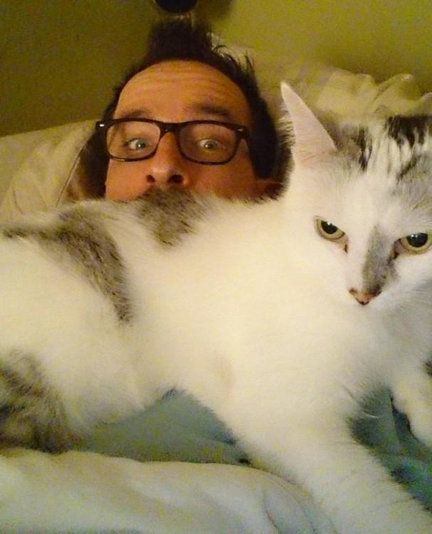 hombre con lentes con gato durmiendo encima