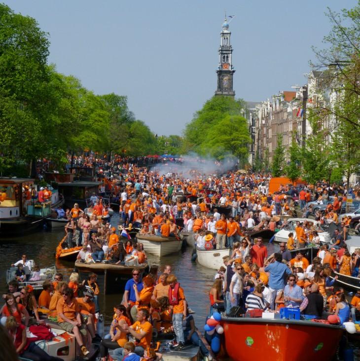 personas vestidas de naranja en unas canoas que van por un canal de agua