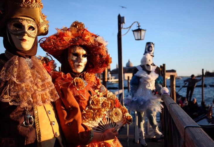 personas con atuendos extravagantes usando mascaras y caminando por las calles de Venecia