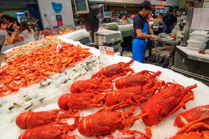 langostas en hielo puestas a la vienta en un mercado de peces