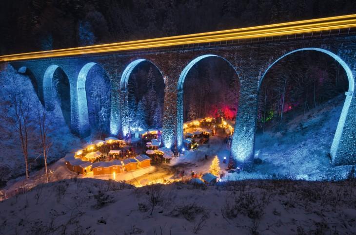 tiendas de un mercado bajo el puente iluminado con luces de navidad en Alemania