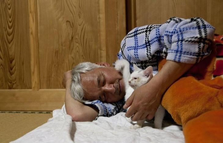 hombre japones durmiendo con gato blanco