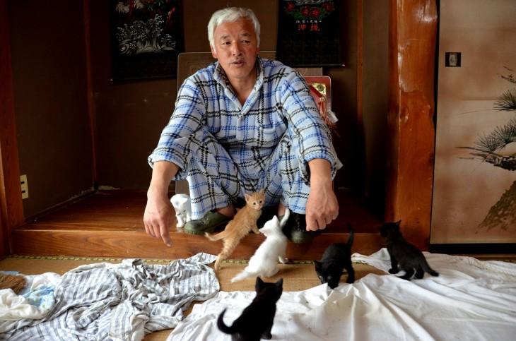 japones con gatitos alrededor en el piso