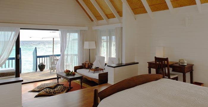 habitación de un hotel con cama y una pequeña sala en su interior