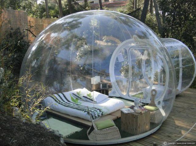 capsula de hule con una cama dentro de ella en medio de un bosque