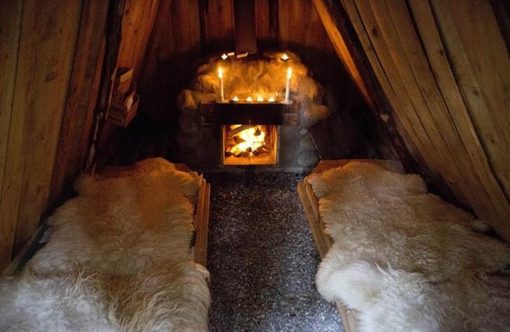 cabaña que cuenta con una chimenea y camas hechas con piel de animales