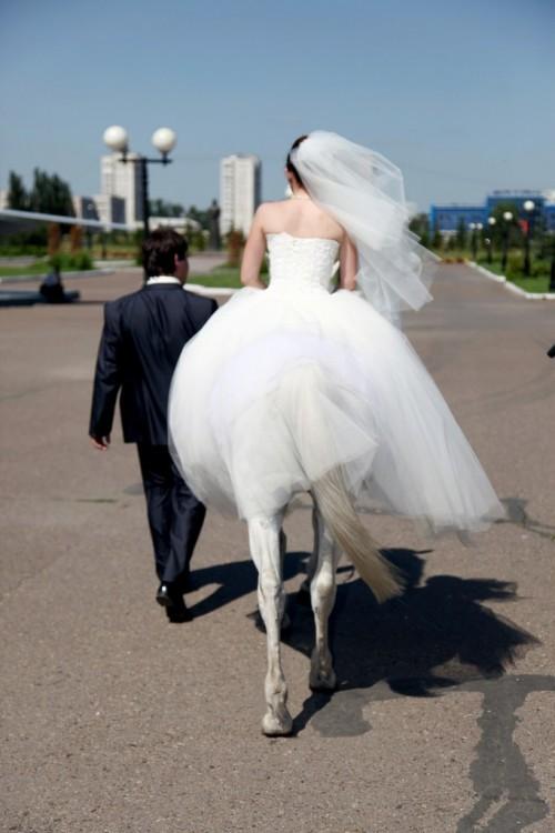 Pareja de novios donde la novia sobre un caballo simula ser un centauro con vestido de novia