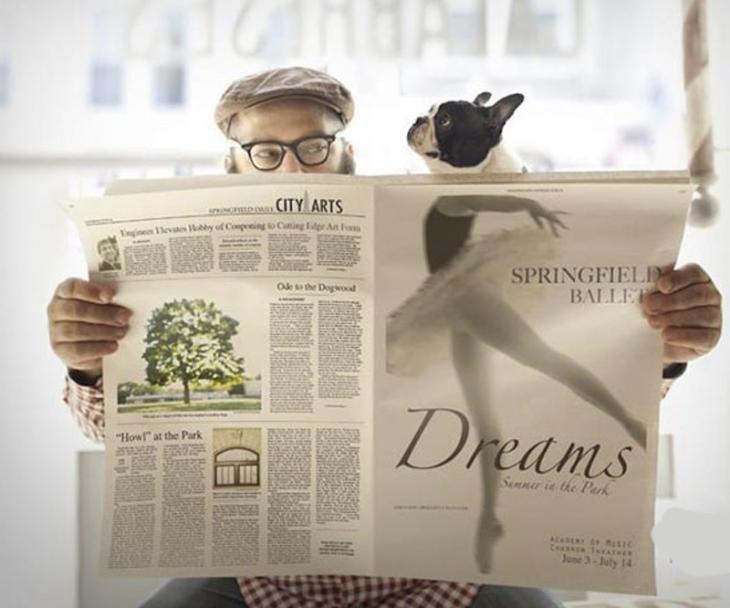 Un hombre extendiendo un periódico con la cara de un perro que esta a su lado simula estar bailando ballet