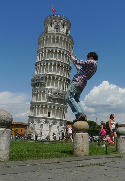 chico con camisa escocesa sostiene la torre de Pisa