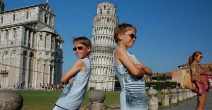 dos hermanos recostados a la torre de Pisa