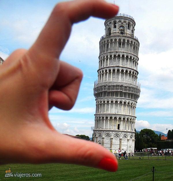dedos apretando a la torre de Pisa