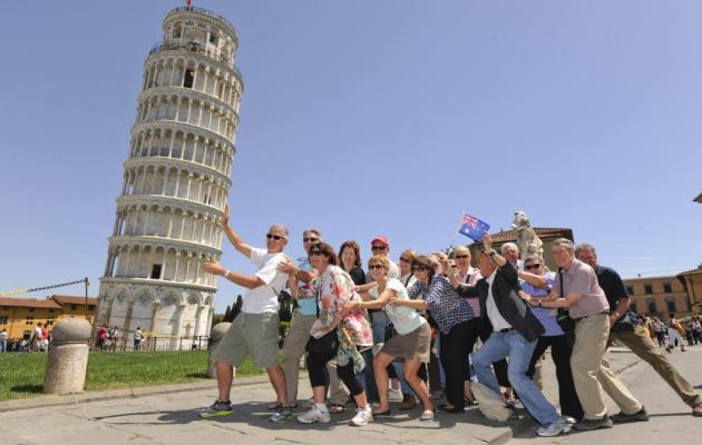grupo de turistas sostiene a la torre de Pisa