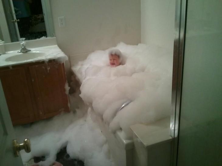 niño en la bañera rodeado de espuma