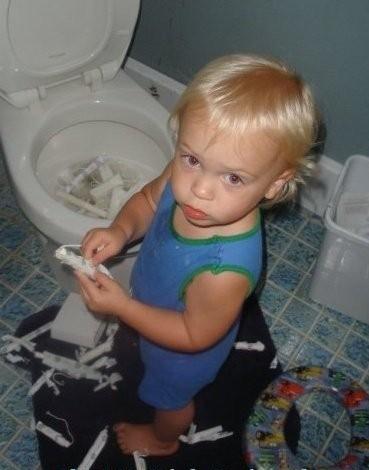 niño llenando el retrete de papel