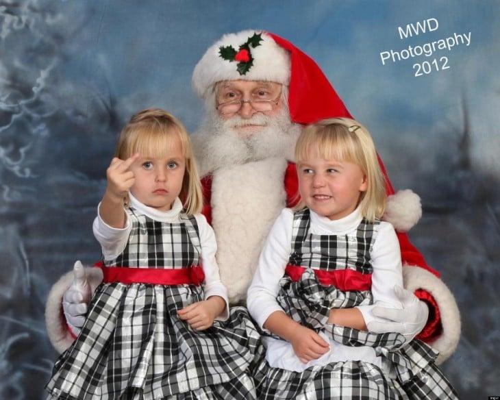 niña sentada junto a su hermana y santa claus
