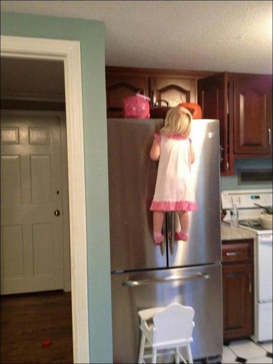 niña sobre una silla colgando de un refrigerador
