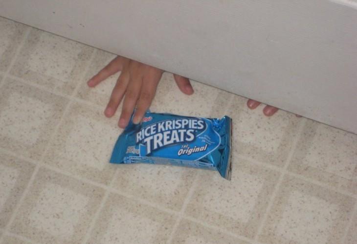 niño tomando un paquete de galletas abajo de la puerta