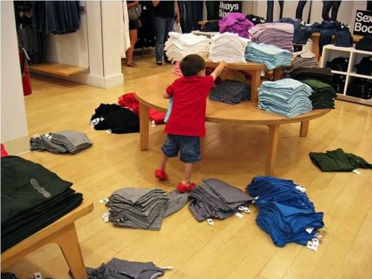 niño desacomodando la ropa de un estante y tirándola al suelo