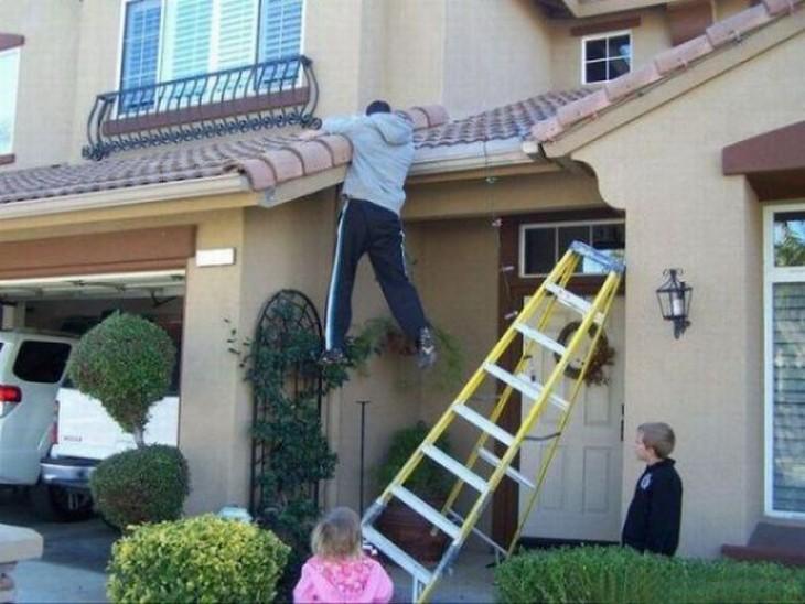 persona colgada del techo de una casa con una escalera a un lado y niños que lo están observando