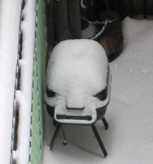 asador de carne cubierto de nieve en el patio de una casa