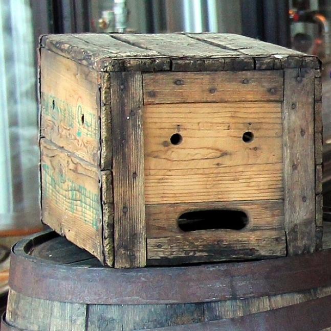 caja sobre un barril que tiene agujeros que forman una cara sorprendida