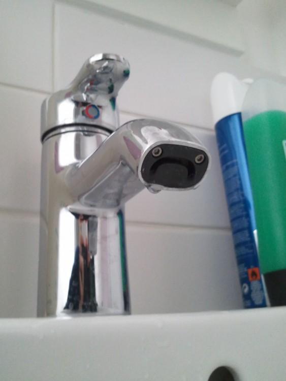 llaves del grifo de un lavabo de baño que forma una cara triste