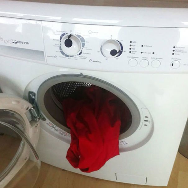 lavadora de color blanco con un trapo rojo saliendo de ella