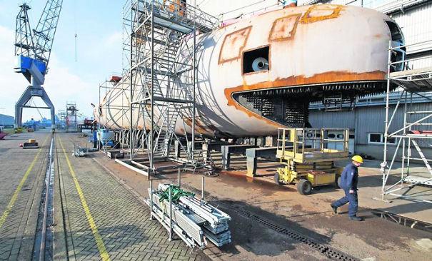 submarino con partes oxidadas sobre una plataforma de metal en un puerto