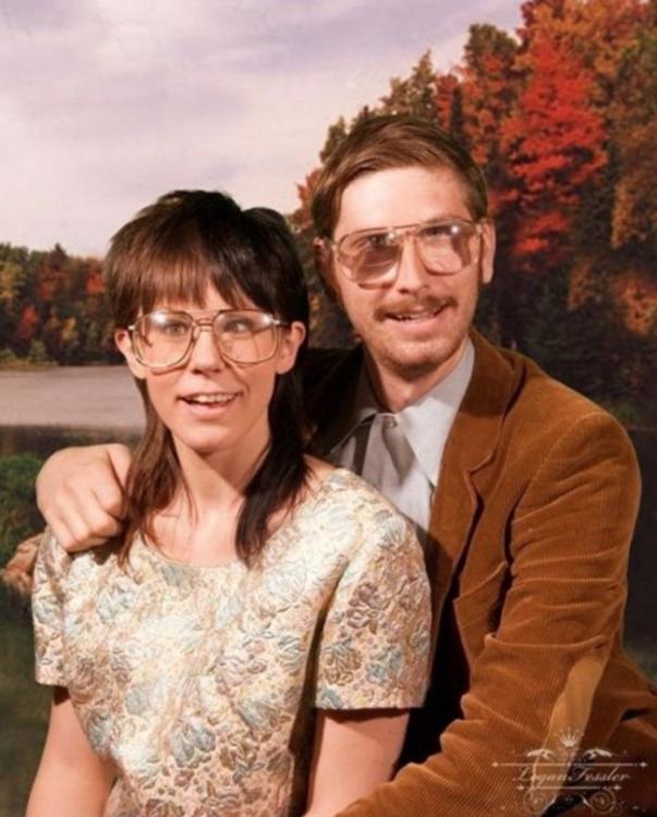 pareja sentados usando gafas mientras posan para una fotografía