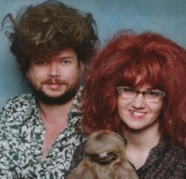 pareja sosteniendo a un perezoso para que sean fotografiados
