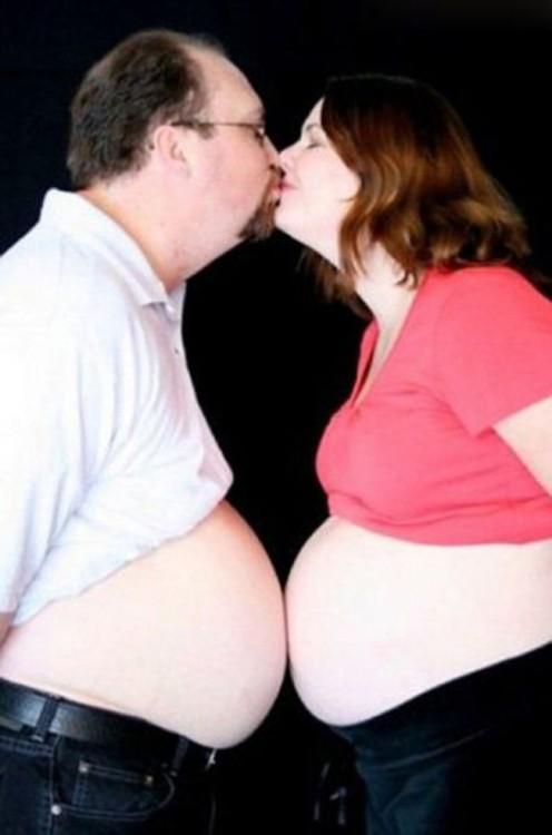 embarazada besando a su esposo mientras tienen el vientre juntos