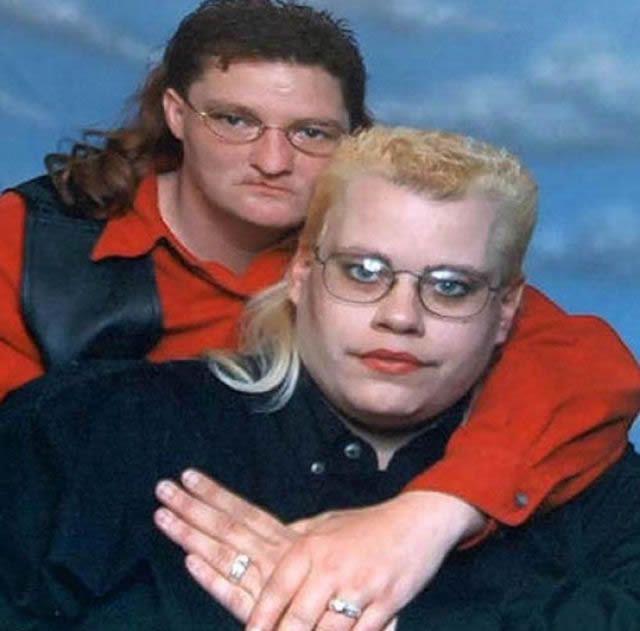 hombre y mujer con el mismo corte de cabello abrazados mostrando sus anillos de boda