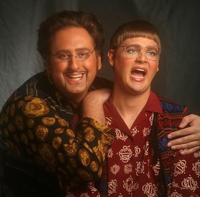 pareja posando para una fotografía, mientras él usa una barba pequeña y ella un copete muy corto