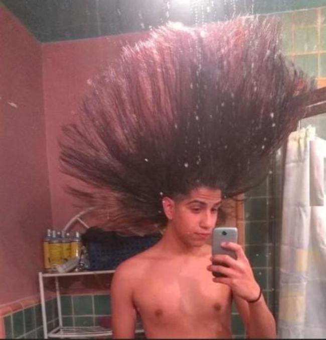 hombre tomándose una foto con el cabello erizado y levantado hacia el techo