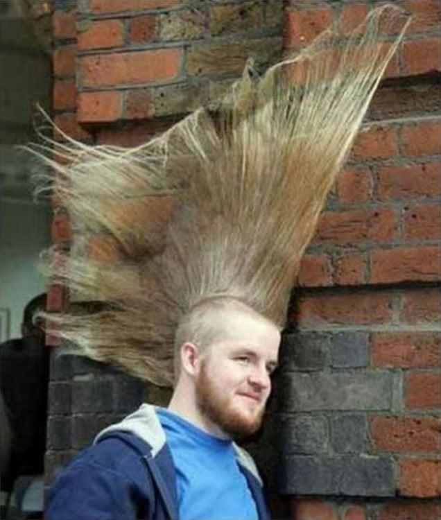hombre con el cabello en moja largo recargado en una pared