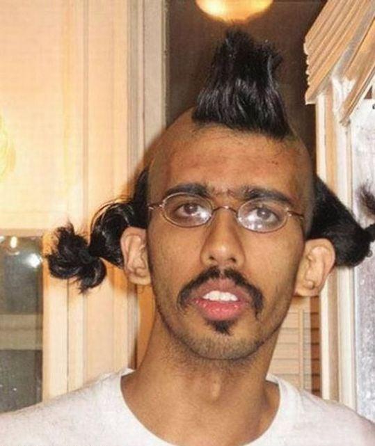 hombre con lentes y con coletas de caballo a los lados y en medio una moja de cabello
