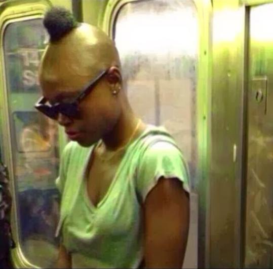mujer en el metro usando una playera color verde