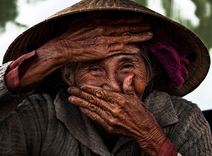 anciana se tapa la boca en vietnam