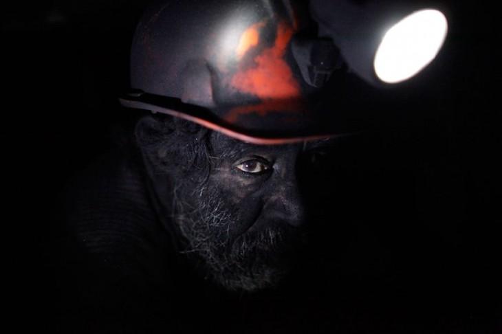 rostro de un hombre minero iluminado con la lampara de su casco
