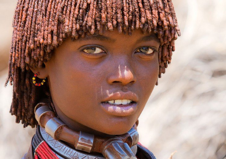 niña de una tribu africana usando collares enormes en el cuello