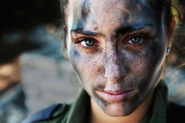 mujer de 18 años con el rostro cubierto de pintura de camuflaje militar