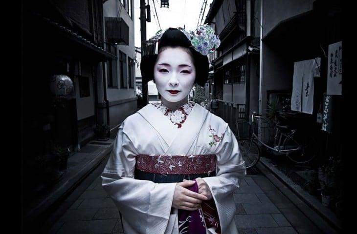 mujer vestida como geisha de color blanco en las calles de japón