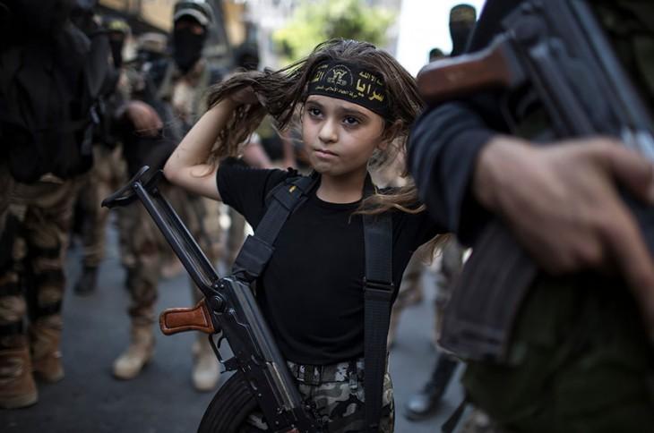 niña con un rifle colgando sobre su pecho mientras ella se toca el cabello