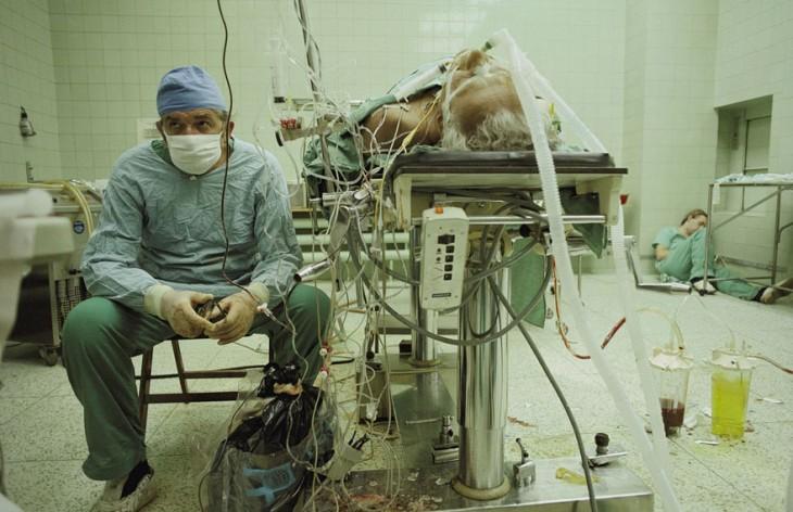 doctor sentado en un quirófano y su asistente durmiendo al fondo luego de 23 horas de operación al realizar un trasplante