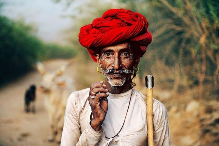 hombre rabari usando un turbante en la cabeza de color rojo mientras esta parado sobre un camino