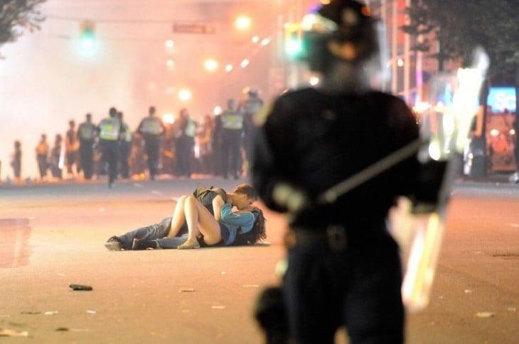 pareja de novios recostados en la acera besándose mientras hay una guerra frente a ellos