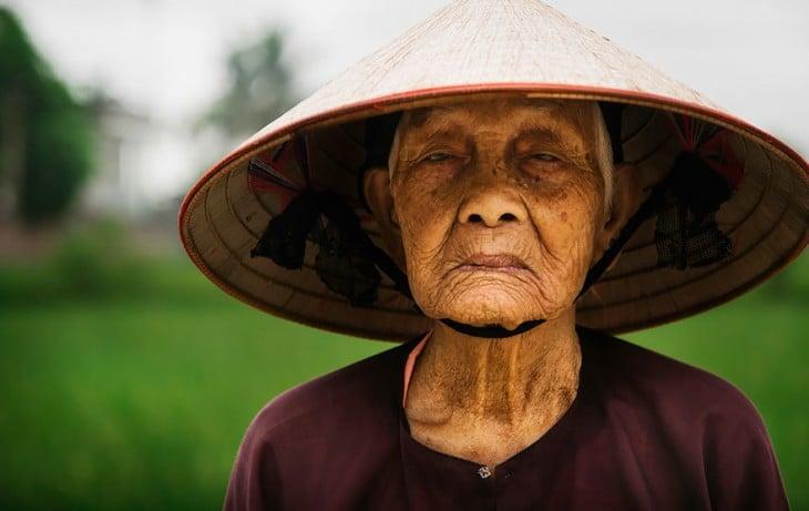 mujer usando un sombrero mientras esta en un campo de cultivo de arroz