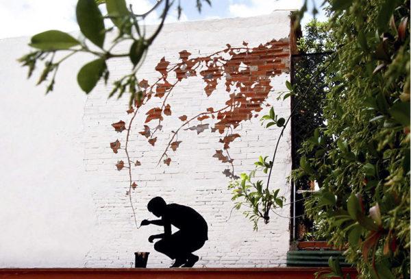 pintura de hombre pintando ramas de un árbol en una pared