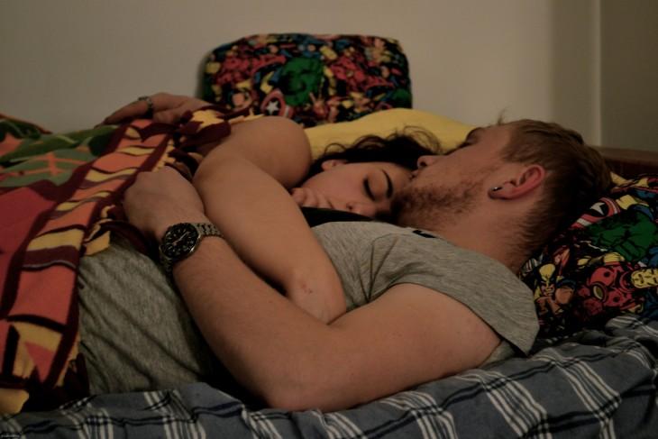 pareja durmiendo abrazados  y mochila de colores al fondo